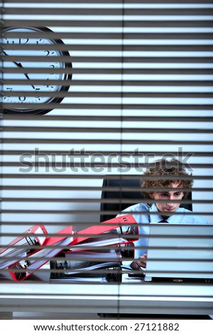 Businessman working at desk behind a windows blinds - stock photo