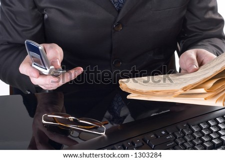 Businessman working at his desk and reading a newspaper - stock photo