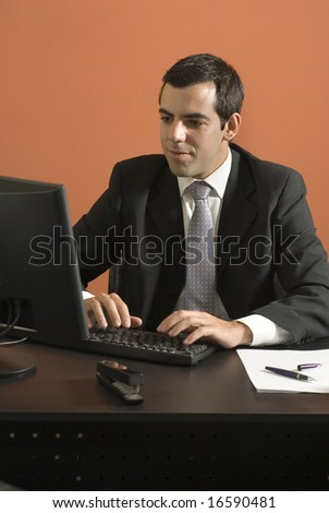 Businessman working at his desk on his computer. Vertically framed photo. - stock photo