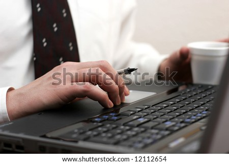 Businessman working at his laptop computer with a pen in one hand and coffee in the other – can represent office work, research, etc. (shallow focus point on foreground hand with pen). - stock photo
