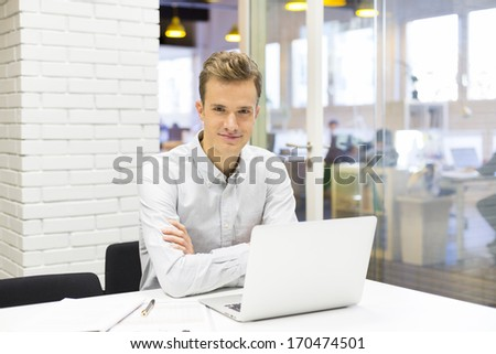 Businessman working at his laptop on the office in start-up, looking camera - stock photo