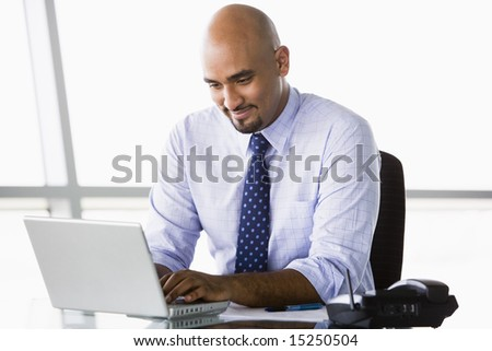 Businessman working at laptop in office - stock photo