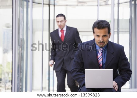 Businessman working at laptop outside - stock photo