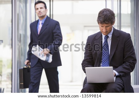 Businessman working at laptop outside office - stock photo