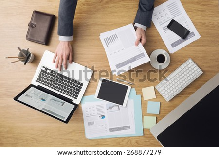 Businessman working at office desk and checking financial reports with computers and paperwork around, top view - stock photo