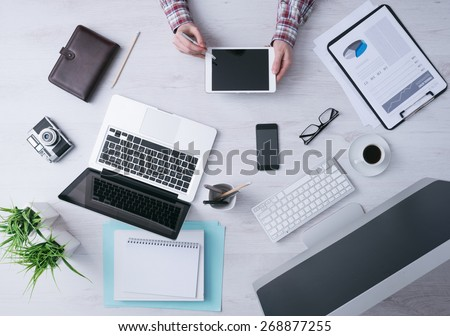 Businessman working at office desk and using a digital tablet, computer, laptop and various objects all around, top view - stock photo