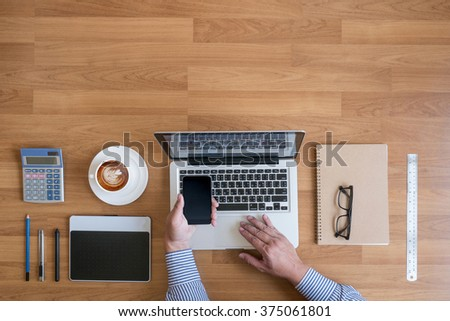 Businessman working at office desk and using a phone touch screen hands detail with other objects around, coffee,  top view,free copyspace - stock photo