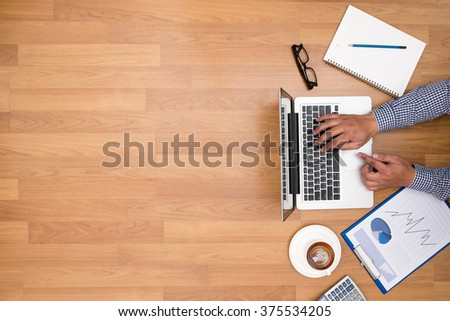 Businessman working at office desk and using computer and objects on the right, coffee,  top view, with copy space - stock photo