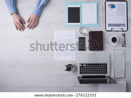 Businessman working at office desk hands detail with copyspace and various objects on the right, top view - stock photo