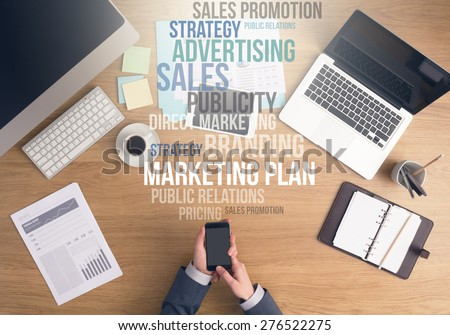 Businessman working at office desk, hands using a smart phone top view, marketing and business text concepts above desktop - stock photo