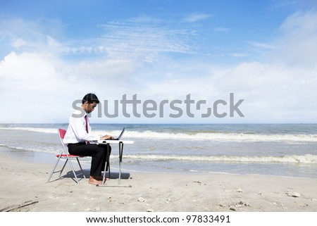 Businessman working at the beach with laptop computer - stock photo