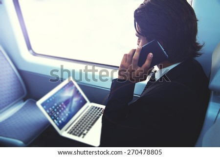 Businessman working busy with laptop on the way to work while sitting in train next to the window, handsome male having cell phone conversation, business man commuting to work while using technology - stock photo