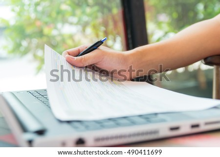 Businessman working by laptop with tablet and smartphone and document on desk, sitting on chair at office