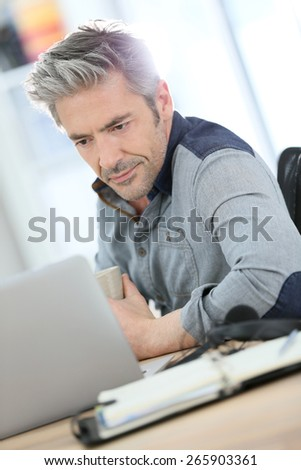 Businessman working form home on laptop computer - stock photo