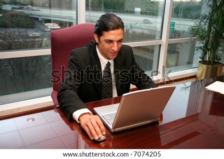 Businessman working in an office dressed in a suit - stock photo