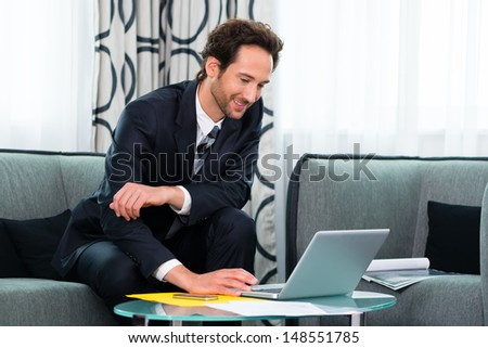 Businessman working in business hotel, he is using wifi to read emails with the computer - stock photo