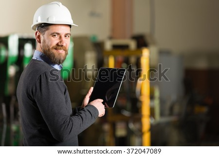 Businessman working in factory. - stock photo