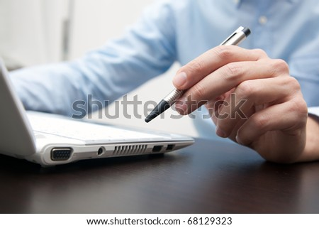 Businessman working in his office holding a pen - stock photo