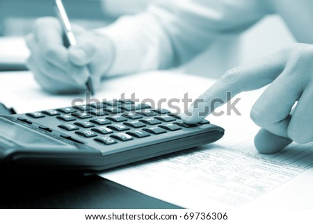 Businessman working in his office with his calculator, blue toned image - stock photo