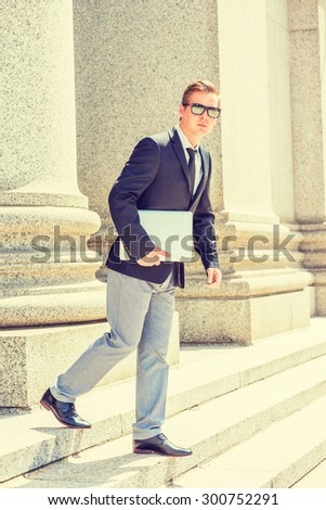 Businessman working in New York. Dressing in black blazer, tie, gray pants, leather shoes, wearing mirror sunglasses, holding laptop computer, a lawyer walking down stairs from office building.  - stock photo