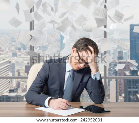 businessman working in office and falling tax papers