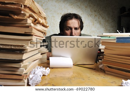 Businessman working in office on laptop. Messy table with a lot of books on. - stock photo