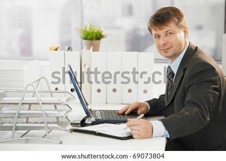 Businessman working in office, using laptop computer. Looking at camera. - stock photo