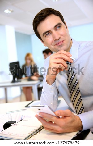 Businessman working in office with electronic devices - stock photo