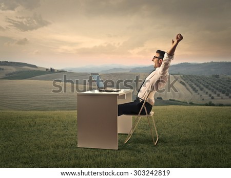 Businessman working in the countryside - stock photo