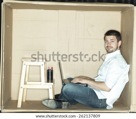 businessman working on a computer in a cramped office - stock photo