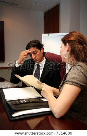 Businessman working on a computer in an office with coworker - stock photo