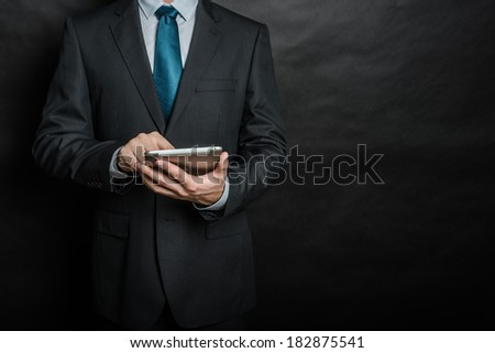 Businessman working on a digital tablet against gray background - stock photo