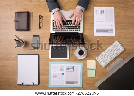 Businessman working on a laptop at office desk with paperwork and other objects around, top view - stock photo