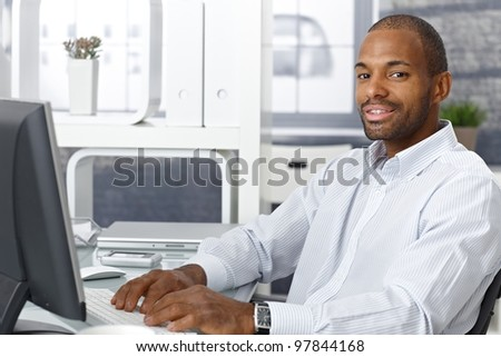 Businessman working on computer at office desk, looking at camera, smiling. - stock photo