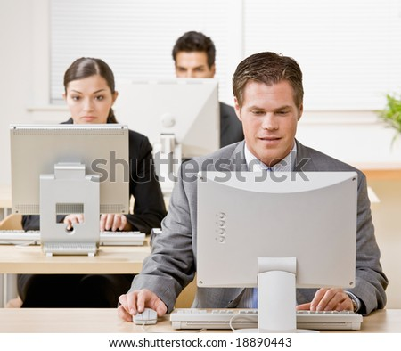 Businessman working on computer with co-workers in background - stock photo