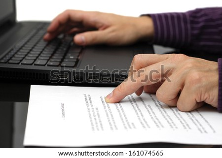 Businessman working on contract with laptop - stock photo