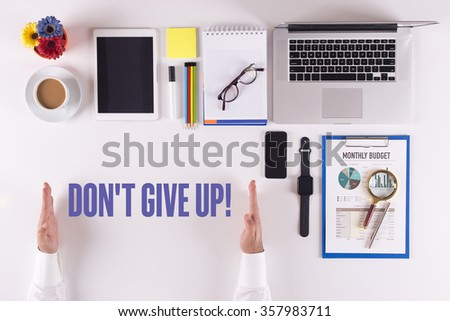 Businessman working on desk - hands showing DON'T GIVE UP! concept - stock photo