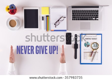 Businessman working on desk - hands showing NEVER GIVE UP! concept - stock photo