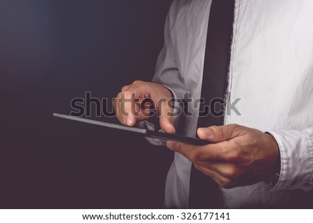 Businessman working on digital tablet computer, finger on touch screen of wireless device, retro toned image, selective focus