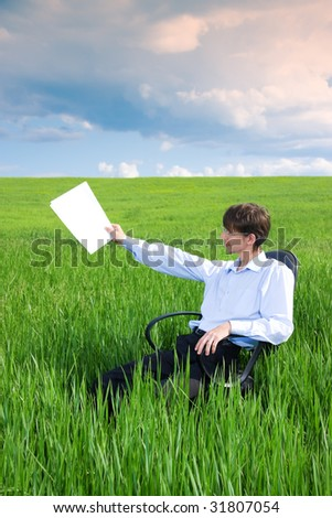 Businessman working on green grassland under blue sky - stock photo