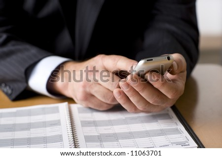 Businessman working on his cell phone.  Shot with shallow depth of field and studio lighting. - stock photo