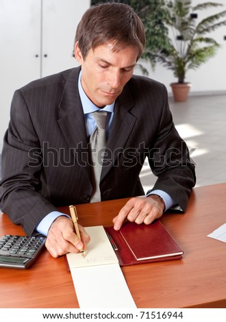Businessman working on his desk in an office environment - stock photo
