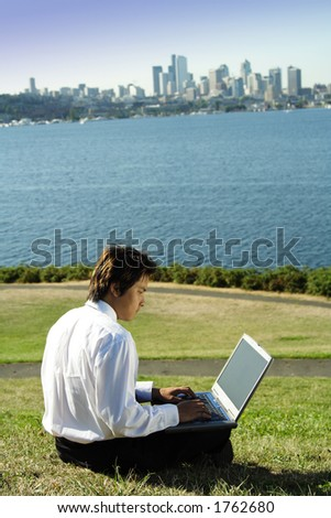 Businessman working on his laptop in a park - stock photo