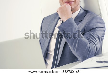 Businessman working on his laptop in the office.Concentrating on the project at hand.Unrecognizable businessman.Selective focus on his body. - stock photo