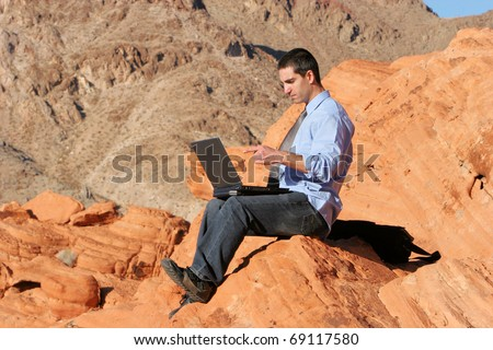 Businessman working on his laptop outdoors - stock photo