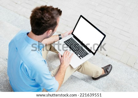 Businessman working on his laptop outside a building - stock photo
