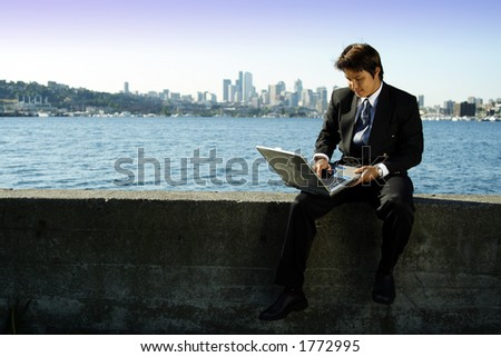 Businessman working on laptop at a park - stock photo