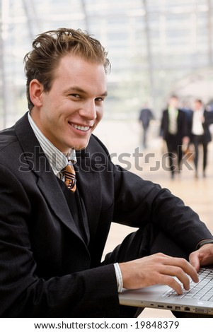 Businessman working on laptop computer at office lobby.