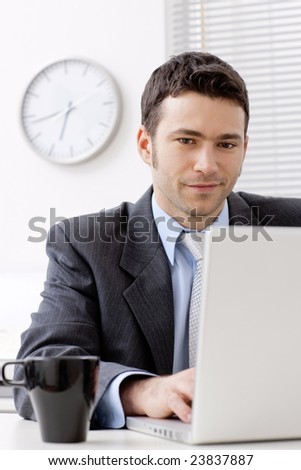 Businessman working on laptop computer at office, smiling. - stock photo