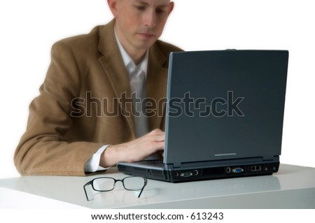 Businessman working on laptop. Focus on laptop, glasses and desk. - stock photo
